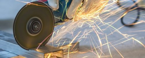 Close-up of worker cutting metal with grinder. Sparks while grinding iron.